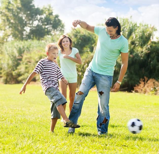 子供とサッカーボールで遊んでいる両親