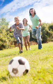 幸せな親とサッカーで遊んでいる少年