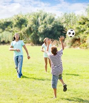 十代の少年とサッカーで遊んでいる幸せな親
