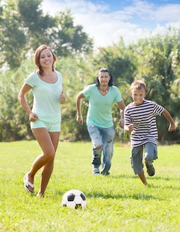 サッカーボールで遊ぶティーンエイジャーの息子の両親
