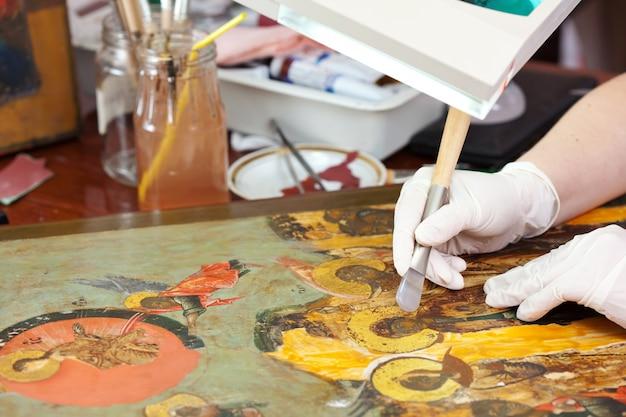 Реставратор позолочен на иконе с агатовой горелкой