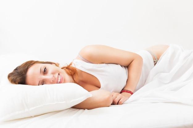 Длинношерстная женщина, лежа на белом листе в постели у себя дома