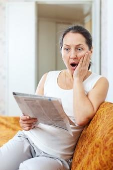 驚くべき成熟した女性は新聞に見える