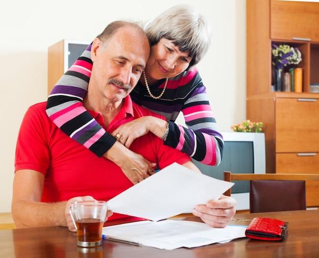 深刻な成熟したカップルが文書を見て