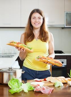 幸せな女の子、調理されたサンドイッチ