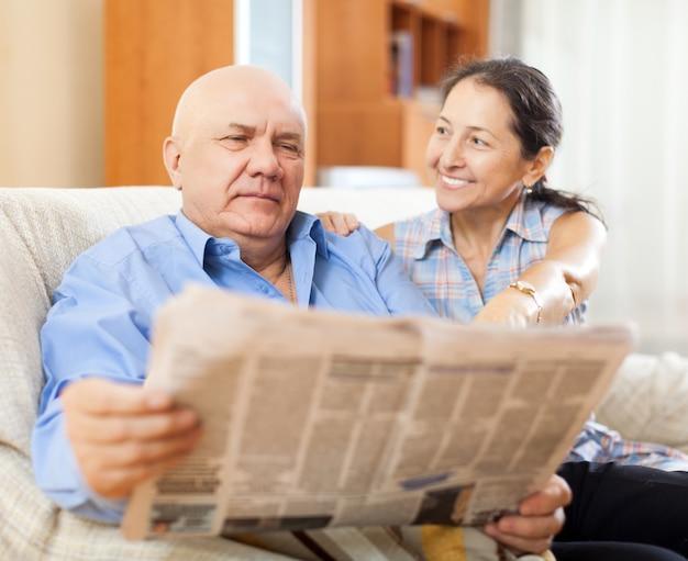 新聞で笑っている成熟した女性と老人の肖像