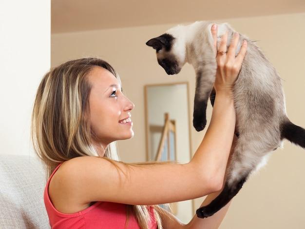 シャムの子猫で遊ぶ女の子