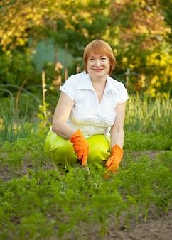 植物の庭で働く幸せな女性