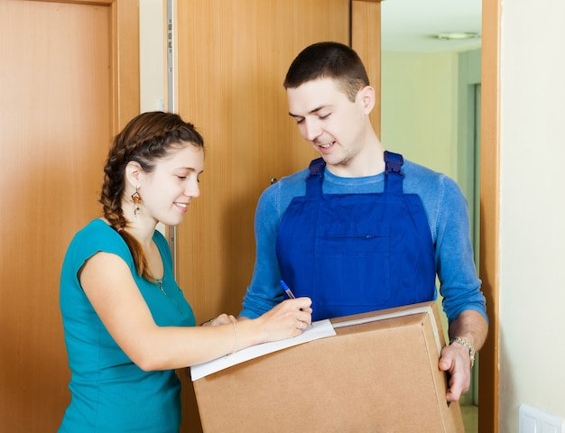 ユニフォームの郵便配達員が小包を小包に配達