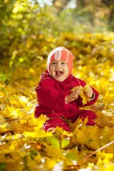 Счастливый малыша, сидящего на кленовых листьях