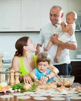 Семья из четырех человек вместе на кухне готовит пищу