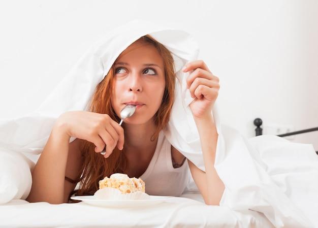 彼女のベッドでビスケットを食べる少女