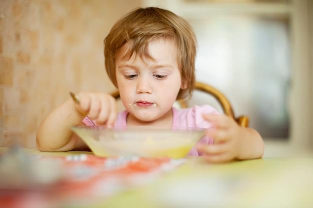 子供が家庭でスプーンで食べる