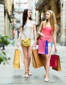 Две девушки ходят с покупками