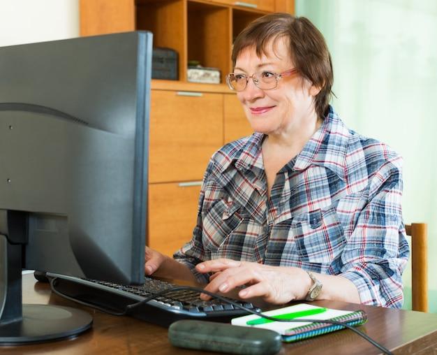 コンピュータで働く高齢者の女性