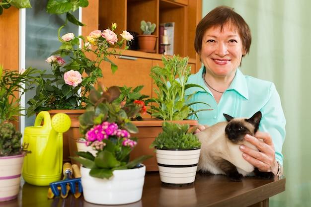 猫と花の植物を持つ女性