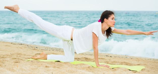 Улыбка взрослая женщина в белой футболке делает упражнения на выносливость