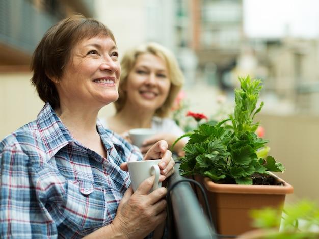 コーヒーを持つバルコニーの老婦人