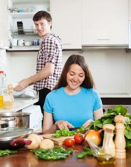 人が皿を洗っている間に料理を作る女性