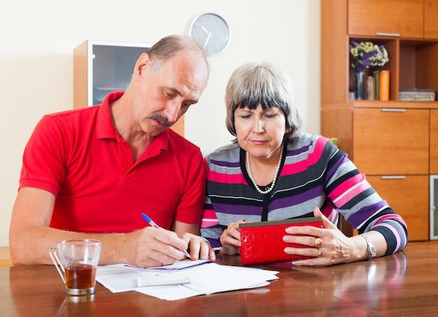 悲しい年配のカップルは、予算を計算する