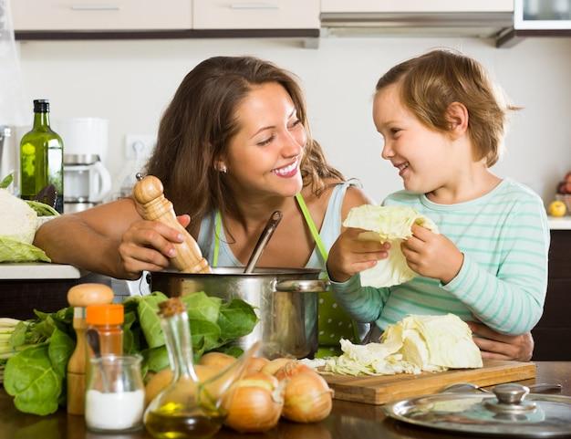 家庭で小さな娘を料理する母親