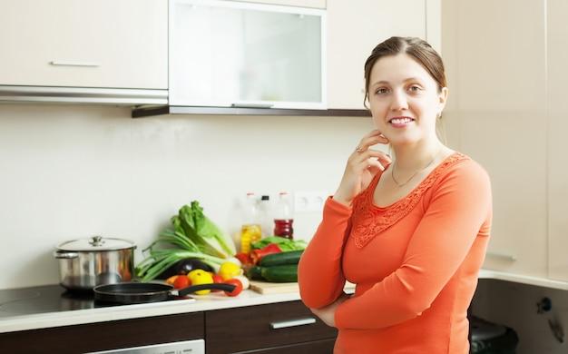 家庭のキッチンで笑顔の女性