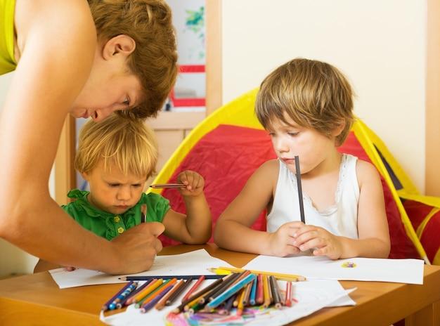深い母親と子供たちが鉛筆で描く