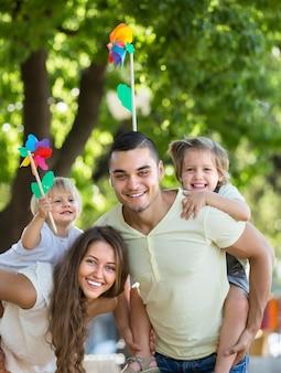 公園でおもちゃの風車を持つ家族