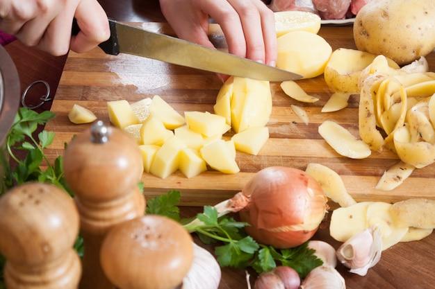 女性の手を切るジャガイモ