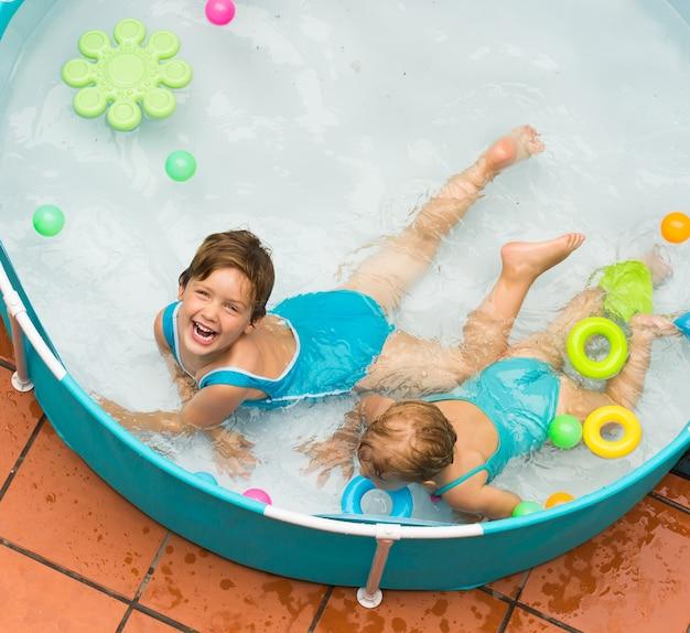 子供プールで泳いでいる子供たち