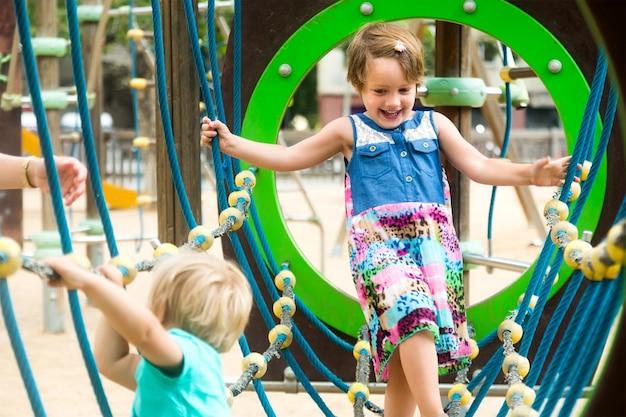 公園の遊び場にいる小さな姉妹