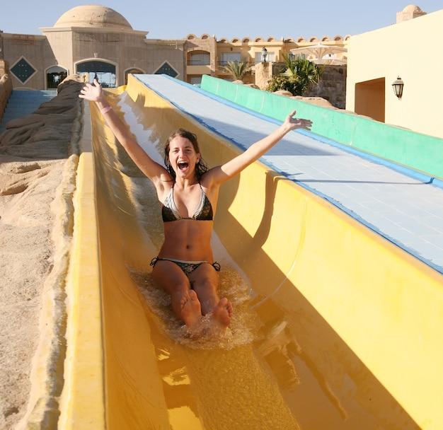 スイミングプールの水のスライドの女の子
