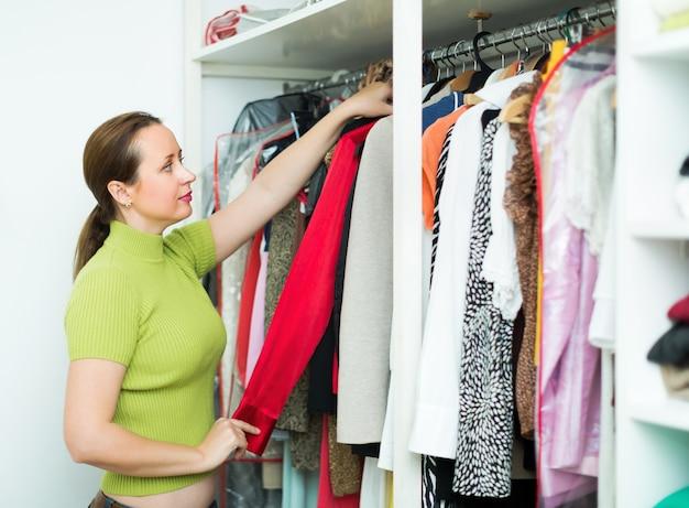 Женщина устраивает одежду в шкафу