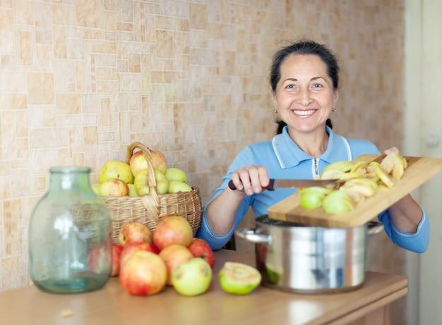 熟した女性がリンゴソースジャムを調理する