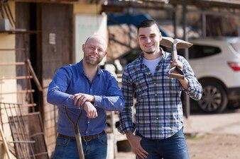 Два фермера, стоящие с лопатами
