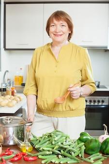キッチンにオクラのヒープを持つ女性
