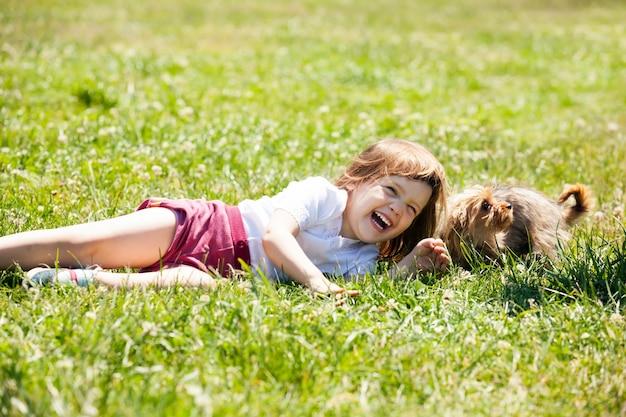 夏、牧草地で子犬と遊んでいる幸せな子供