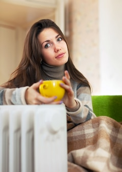 Женщина рядом с масляным обогревателем
