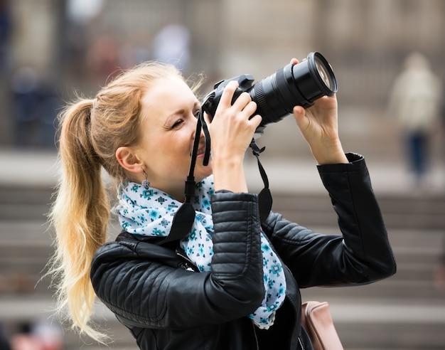 デジタルカメラで秋の街を歩く女性