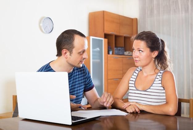 ペーパーとノートパソコン付きの机のカップル