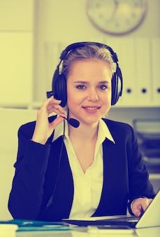 女性の顧客サポート電話オペレータの職場で