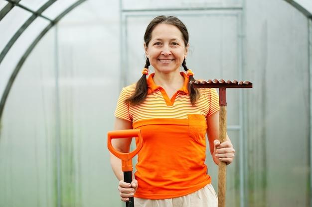 温室に庭のツールを持つ女性