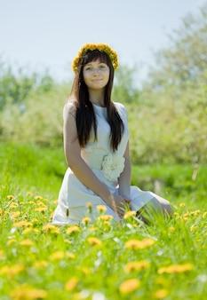 タンポポの牧草地に座っている女の子
