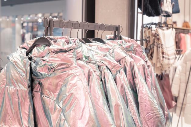 Одежда на вешалках в модном магазине.