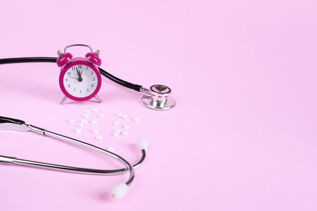 コピースペースとピンクの丸薬、聴診器、目覚まし時計。医学は薬を服用する時です。
