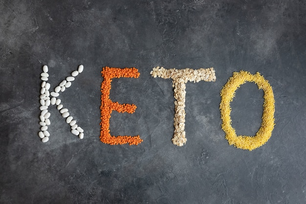 Кето слово из кетогенной пищи. кето, кетогенная диета, низкий уровень углеводов. вид сверху здоровой пищи. органические продукты: чечевица, овсянка, фасоль, просо на темно-сером.