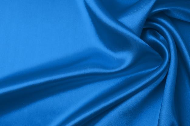 トレンディな古典的な青い色の繊維とテクスチャの概念。古典的な青い色-クローズアップの波状のシルク生地のサンプル。
