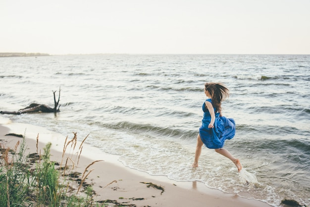 海の海岸の若い美しい女性。