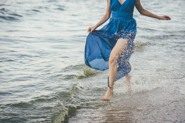 Красивая женщина вдоль кромки воды.