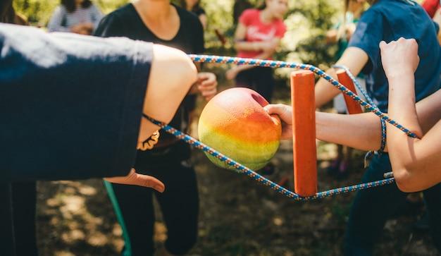 若い人たちはお互いにピンと張ったロープを使ってボールを渡します。チームビルディング演習、チーム精神。チームの関係を強化する。人々のチーム間の統一